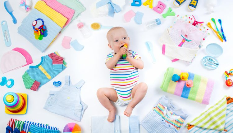 Little baby with clothing and infant care items
