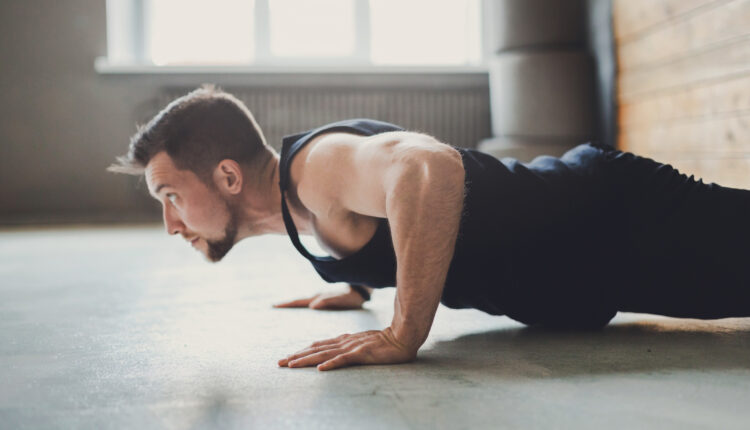 Young man fitness workout, push ups or plank