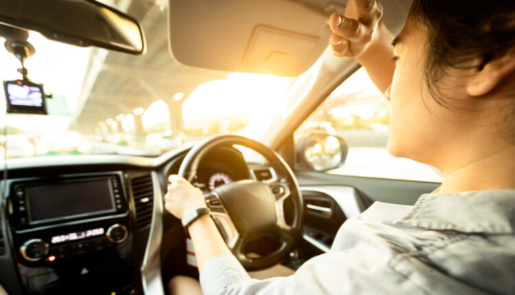 Asian female driver covering face by hand of bright sun,disturbe