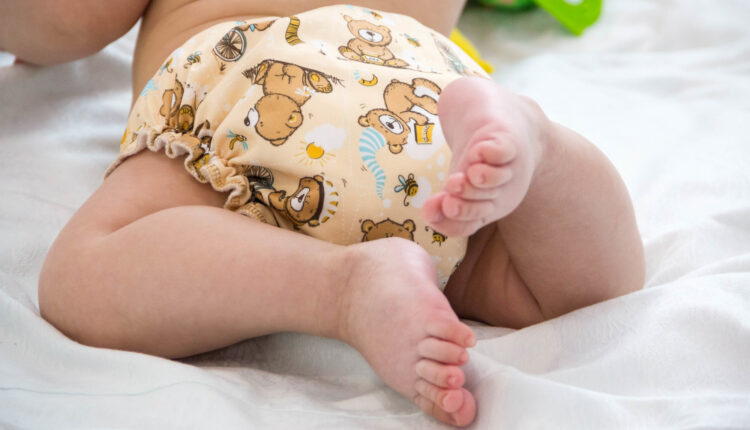 baby in modern eco stacks of cloth diapers and replacement bushings selective focus close-up on bright background, little cute foot kid, the concept of health. hygiene of the child. reusable diapers